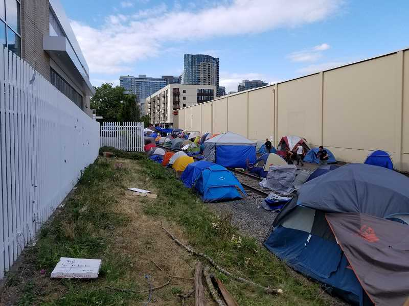 REVIEW PHOTO: ANTHONY MACUK - Tents line the area on either side of the trolley track, and the area has served as a hub for the protesters when they're not demonstrating out on the street and sidewalk in front of the ICE headquarters.