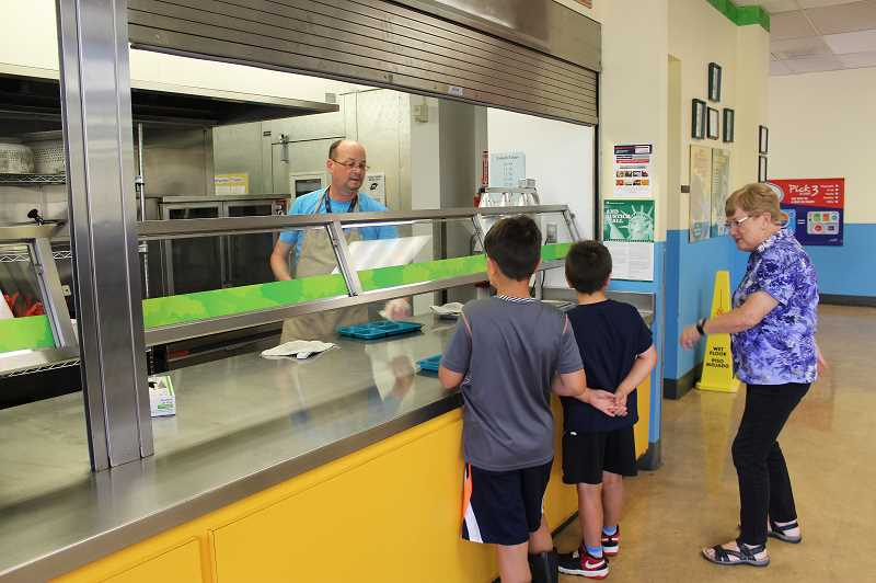 HERALD PHOTO: KRISTEN WOHLERS - James Moore (left) serves up lunch to kids at Knight Elementary on June 28 while volunteer Linda Kristensen chats with them.