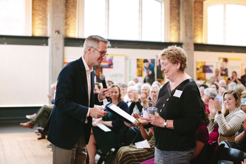 COURTESY: ASHLEY COURTER - Mayor Ted Wheeler proclaims June 21 'Outside In Day,' and hands a proclamation to Executive Director Kathy Oliver during Outside In's 50th anniversary party.