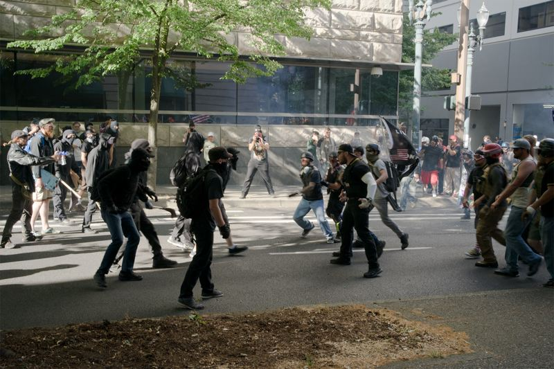 TRIBUNE PHOTO: KIT MACAVOY - Members of Antifa and Patriot Prayer square off during a confrontation in the streets of downtown Portland on Saturday, June 30.