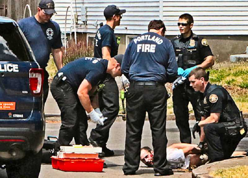 DAVID F. ASHTON - Portland Fire & Rescue paramedics assess the medical condition of the suspect, and provide first aid for the apprehending dog bites, as he's taken into custody.