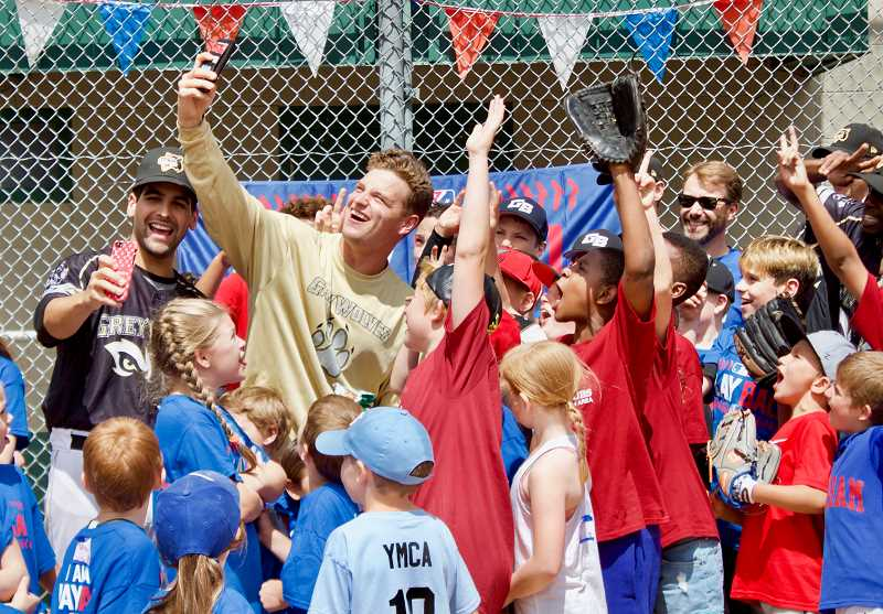 OUTLOOK PHOTO: CHRISTOPHER KEIZUR - Gresham GreyWolves pitcher Jack Gordon, middle, takes a selfie with the kids during Play Ball Gresham.