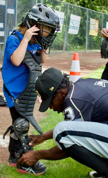 OUTLOOK PHOTO: CHRISTOPHER KEIZUR - Kelechi Anyanweu, second baseman for the Gresham GreyWolves, helped one of the kids try on catcher gear.
