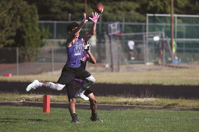 PHIL HAWKINS - Woodburn junior Ethan Ing jumps a passing route against Jefferson and picks off the pass in the Bulldogs' opening game of their 7-on-7 series last week.