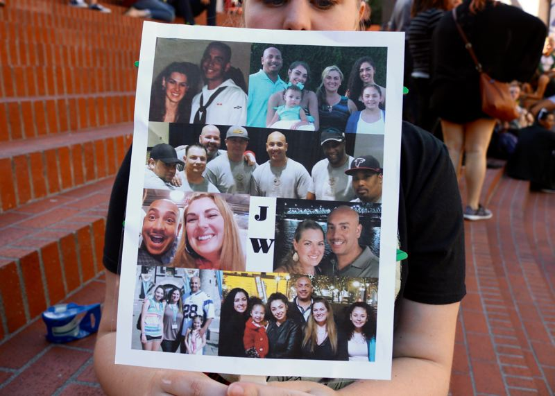 TRIBUNE PHOTO: ZANE SPARLING - A woman holds a sign with pictures of Jason Washington, who was fatally shot by  Portland State University police officers outside the Cheerful Tortoise on July 29.