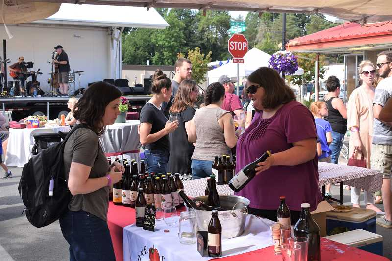 ESTACADA NEWS PHOTO: EMILY LINDSTRAND - Sarah Hamblin of Stone Circle Cider shows the ciderys offerings to an attendee of Estacada Uncorked on Saturday, June 30.