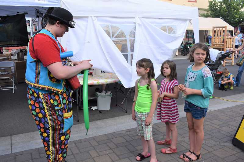 ESTACADA NEWS PHOTO: EMILY LINDSTRAND - Michael Swenson, dressed in clown attire, creates balloon animals for children at Estacada Uncorked.