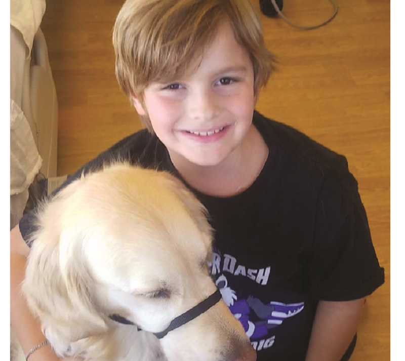 PHOTO COURTESY OF CROOK COUNTY RODDERS - Stryder Doescher poses for a photo with his service dog, Keebler.