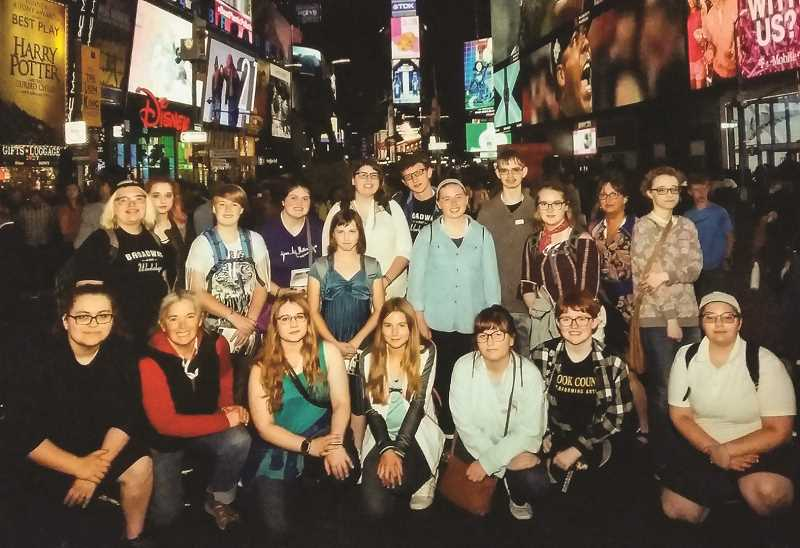 PHOTO SUBMITTED BY  ANITA HOFFMAN - Students and their chaperones have a group photo taken in Times Square. Front row from left to right: Elyssa Orozco, Anita Hoffman, Jenna Porter, Lillian Hoffman, Taylor Wanous, Casey Tunison and Chantrece Worthington. Back row from left to right: Drew Finley, Gala Smith, Erin Crawford, Anna Williamson, Zoe Poor, Katie Jones, Aiden Rictor, Hazel Hoffman, Jayme Pack, Sydney Hacker, Cathy Wilson and Hope Smith.