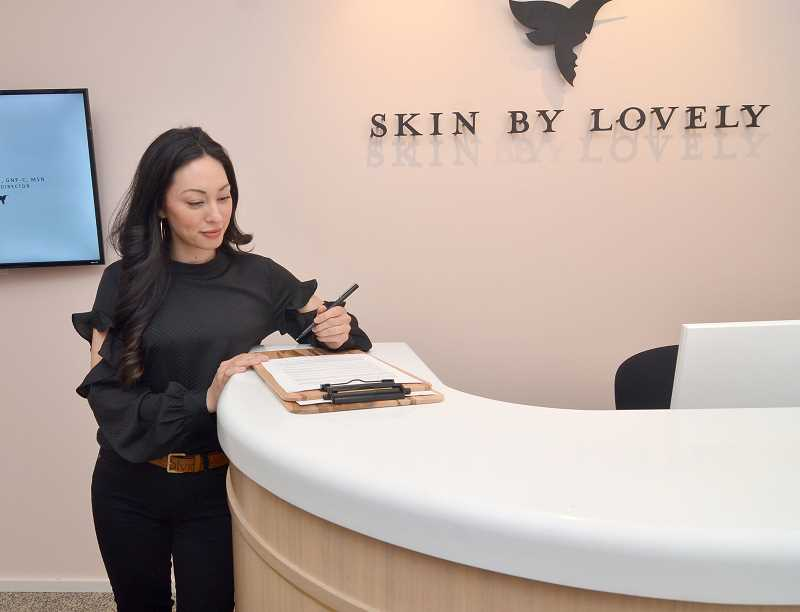 STAFF PHOTOS: VERN UYETAKE  - Skin by Lovely National Development Manager Lisa St. John checks the client log at the new clinic in Lake Oswego.