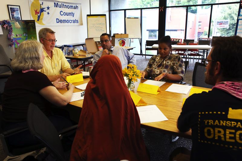 TRIBUNE PHOTO: JESSIE DARLAND  - Rachelle Dixon speaks with volunteers who translate voter information postcards into 11 different languages, something she pushed the Multnomah County Democrats to undertake.