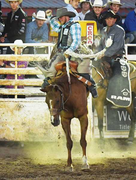 LON AUSTIN/CENTRAL OREGONIAN - Tyrell Smith makes the most of a reride opportunity Saturday, scoring 82.5 points on Sod Buster to win the saddle bronc riding at this year's Crooked River Roundup. Smith, from Sand Coulee, Montana, was fouled exiting the chute on his first ride.