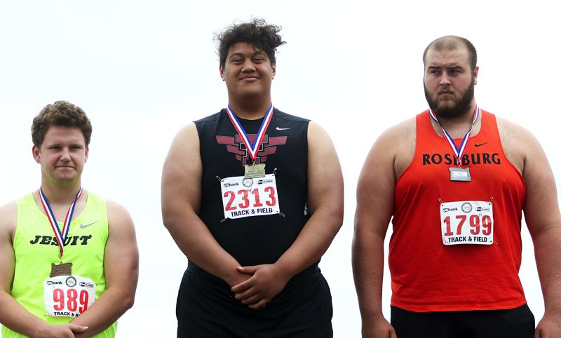 TIMES PHOTO: DAN BROOD - Gerald Saina (center), a 2018 Tualatin graduate, won a title in the shot put event at the Class 6A state track and field championships.