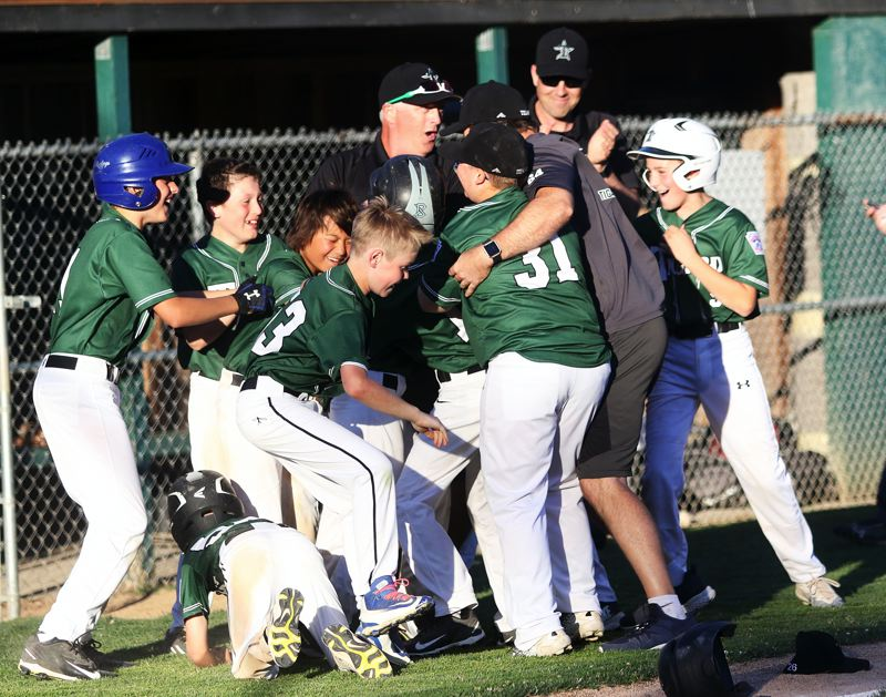 TIMES PHOTO: DAN BROOD - The Tigard Little League ages 9-11 all-star team celebrates following its 7-6 district tournament semifinal win over Lake Oswego on Monday.