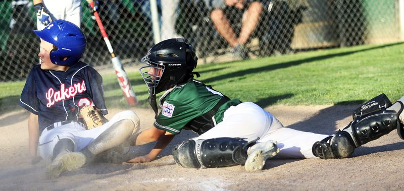 TIMES PHOTO: DAN BROOD - Tigard Little League catcher Owen Wright (right) tags out a Lake Oswego runner at the plate during the seventh inning of Mondays game.