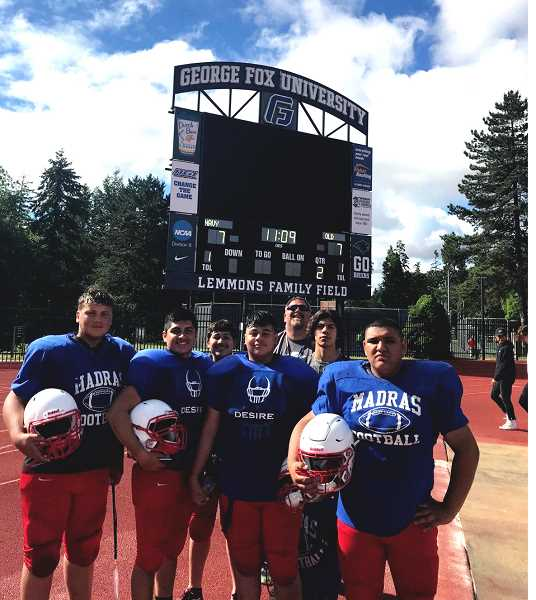 SUMBITTED PHOTO - A group of Madras football players stand before the George Fox University scoreboard.