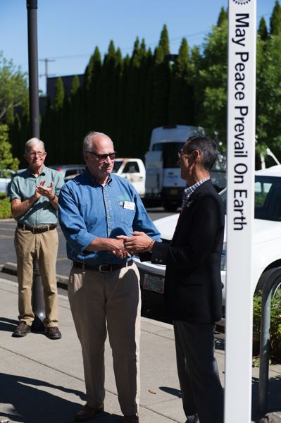 STAFF PHOTO: CHRISTOPHER OERTELL - Mayor Pete Truax of Forest Grove, left, shakes hands with Mayor Haruhito Sasajima of Nyuzen, Japan, after the unveiling of a Peace Pole outside the Forest Grove Community Auditorium.