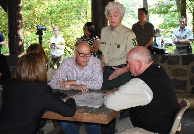 OUTLOOK PHOTO: MATT DEBOW - U.S. Forest Service area manager, Lynn Burditt for the Columbia River Gorge National Scenic area shows a map illustrating the effects of the Eagle Creek Fire to Gov. Kate Brown, Rep. Greg Walden and U.S. Department of Agriculture Secretary Sonny Perdue, far right.
