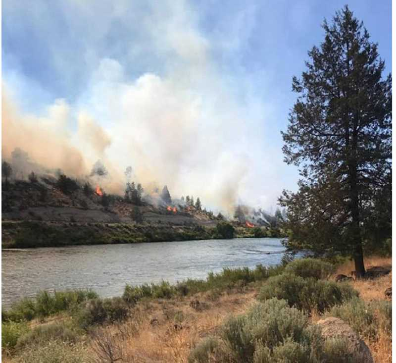 PHOTO BY RYAN GROTE - The Mecca Fire burns along the Deschutes River.