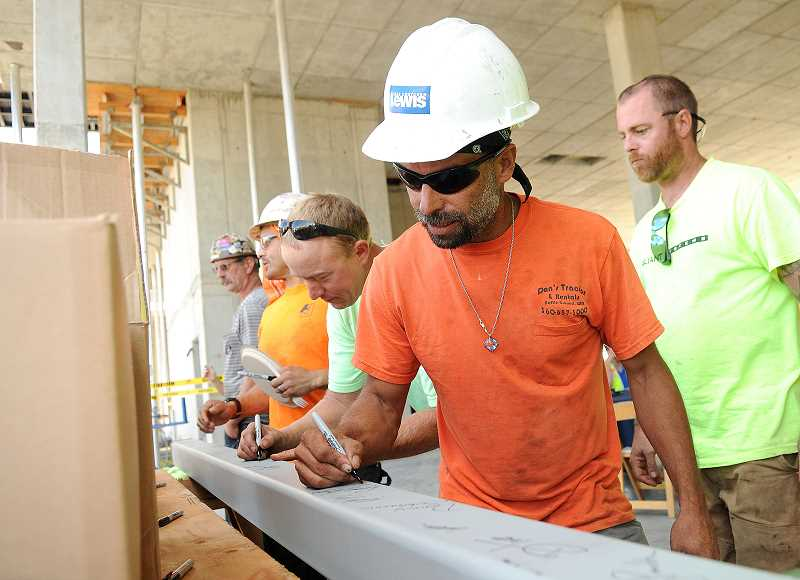 REVIEW PHOTO: VERN UYETAKE - Construction workers sign the final girder at a topping out ceremony in September 2016. They're standing in what is now retail space on the first floor of The Windward building along First Street.