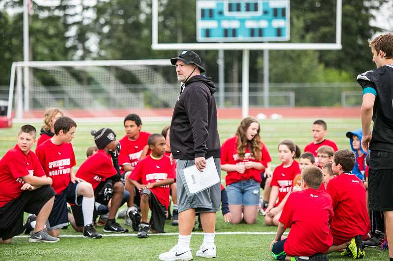 COURTESY PHOTO - Eric Nyborg, founder and Executive Director of Sports Outreach Northwest, talks to a group of kids at a football clinic last year.