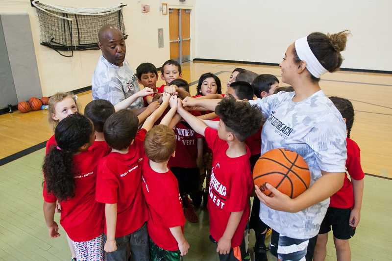 COURTESY PHOTO - Kids huddle with coaches at a Sports Outreach Northwest basketball camp held at Century High School earlier this year.