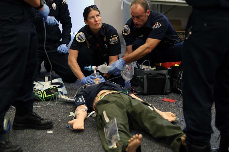 TIMES PHOTO: JESSICA DARLAND - TVF&R's Danielle Joe and Tom Herrington work on a dummy during a training session to learn how to use new emergency medical equipment.