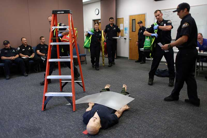 TIMES PHOTO: JESSIE DARLAND - Emergency workers, above, respond to a call of an unconscious 'patient' during their training with the new video laryngoscopy devices, right. Some of those devies will land in new state-of-the-art kits, below.