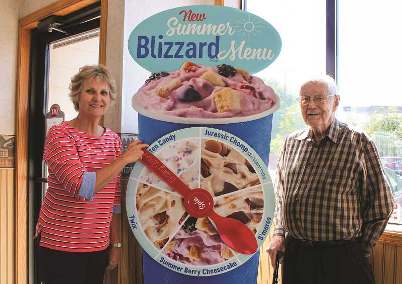 HOLLY SCHOLZ/CENTRAL OREGONIAN   - Jeri Fawbush, left, and Gene Fawbush have owned the Prineville Dairy Queen restaurant since January of 1979. They stand next to a display showing the five new summer Blizzard flavors.