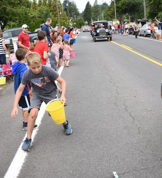 OUTLOOK PHOTO: MATT DEBOW - Cade Holwege runs to collect candy during the Corbett Fun Fest Parade on Wednesday July 4. Cade has attended the annual Independence Day celebration in Corbett since he was a baby.