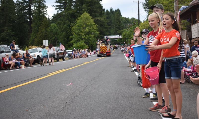 OUTLOOK PHOTO: MATT DEBOW - Hailey De Leon, 11, far right, wishes passing floats a 'Happy Fourth,' while holding out a bucket asking for candy during the Corbett Fun Fest Parade on July 4, while Ella Holwege, 11, waves at passing parade entries.