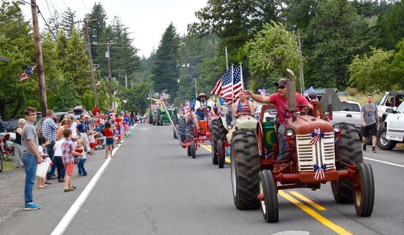 OUTLOOK PHOTO: MATT DEBOW - Dan Graff throws candy to parade watchers while driving a tractor on the parade on Wednesday, July 4.