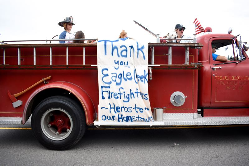 OUTLOOK PHOTO: MATT DEBOW - An old fire engine travels down the route for the annual Corbett Fun Fest Parade on July 4. A sign draped to the side of the truck reads, Thank you Eagle Creek Firefighters — Heroes to Our Hometown.