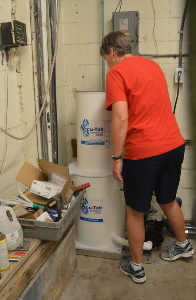 SPOTLIGHT PHOTO: NICOLE THILL-PACHECO - Pool manager Anne Scholz examines a new chlorine tablet-based system recently installed at Eisenschmidt Pool, replacing a liquid chlorine system. The new system is expected to save close to $12,000 annually, Scholz explained.