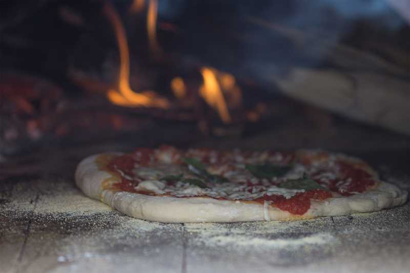 TIMES PHOTO: KIT MACAVOY - A margherita-style pizza is placed in the oven to cook.