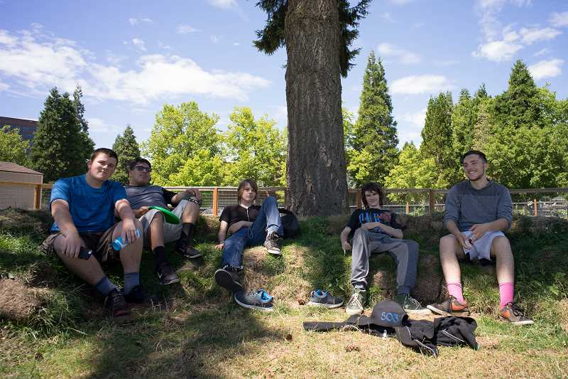 TIMES PHOTO: KIT MACAVOY - From left to right: Isaiah Schwab, Luis Zuniga, Tyson Olsen, Austin Smith and Andrew Faulkenberry rest in the shade on an earthen bench while waiting for the cob oven to produce its first pizzas.