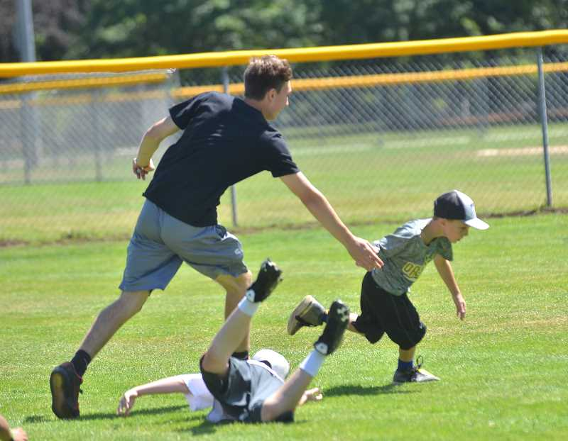 SPOKESMAN PHOTO: VERN UYETAKE  - Lukas Schimmerfield tags Loki Modmore at the Skyhawks baseball camp at Memorial Park.
