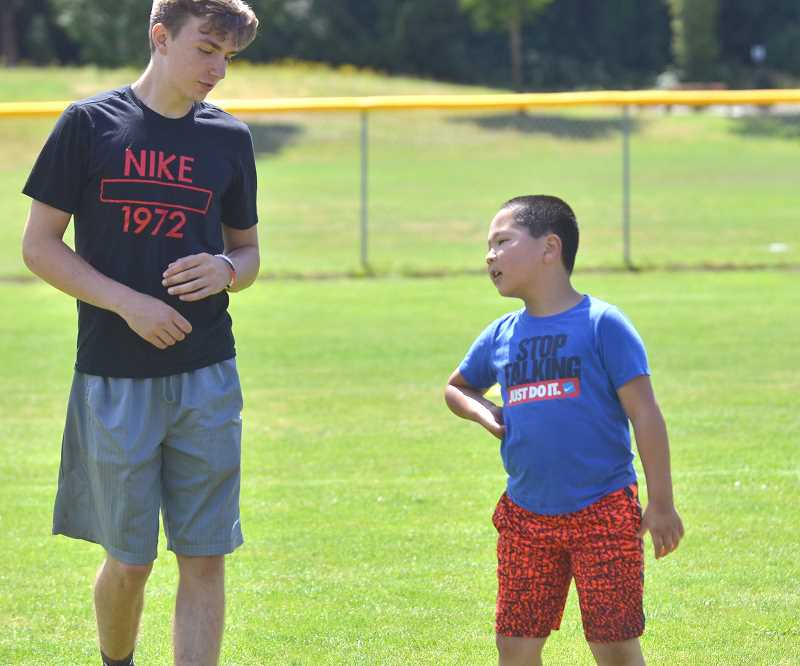 SPOKESMAN PHOTO: VERN UYETAKE  - Lukas Schimmerfield chats with Trey Seid during the Skyhawks baseball camp at Memorial Park.
