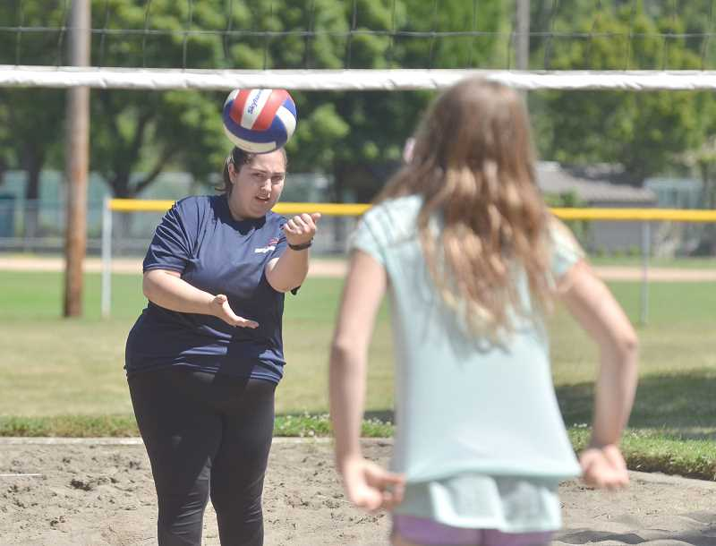 SPOKESMAN PHOTO: VERN UYETAKE  - Volleyball instructor Kirsten Wright serves the ball during the Skyhawks volleyball camp at Memorial Park.