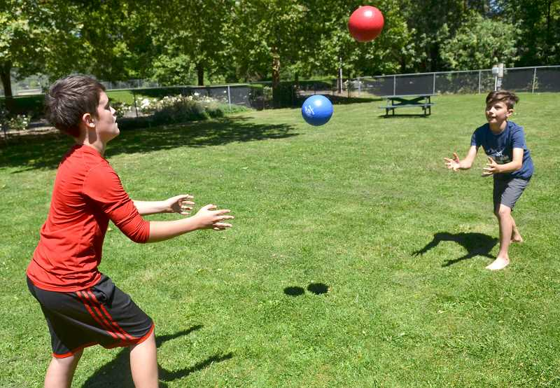 TIDINGS PHOTO: VERN UYETAKE  - Levi Monego, left, and Brennan Jarrell toss the ball back-and-forth during the Fun in the Sun camp.