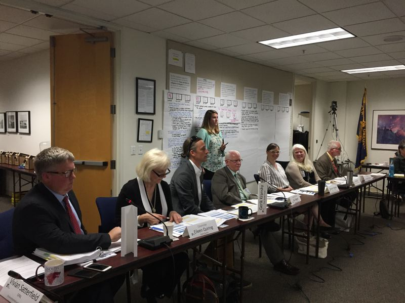 PARIS ACHEN/CAPITAL BUREAU - Members of a policy advisory committee discuss their recommendation to the Oregon Transportation Commission for tolling Interstate 5 and Interstate 205 in the Portland area. On the wall, are some of the issues they addressed in their report.