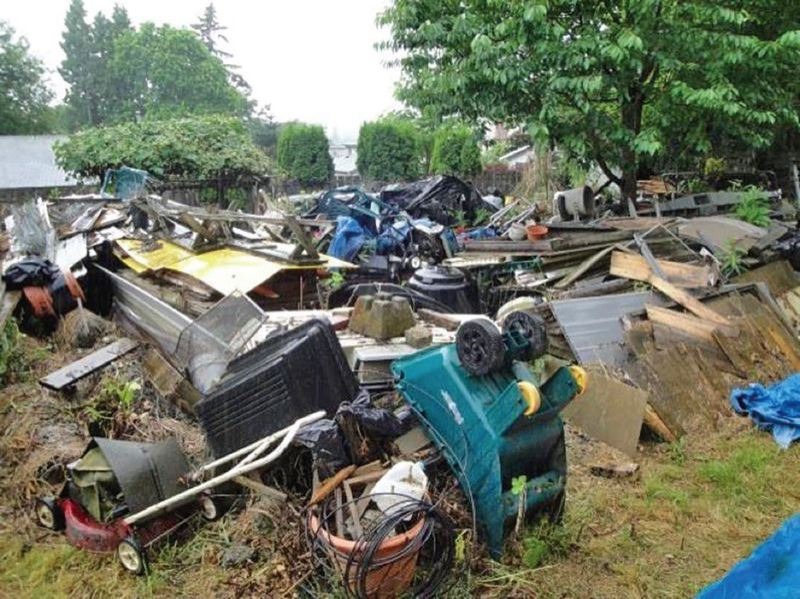 PORTLAND TRIBUNE FILE PHOTO - The yard of a property owned by Norman Yee in Milwaukie when the Portland Tribune first wrote about him two years ago.  It took the city four days and 20 truckloads to clear the junk, including 24,000 pounds of wood, 10 riding lawnmowers and 81 other pieces of lawn-care equipment. The final lien assessed for the work was $17,732.