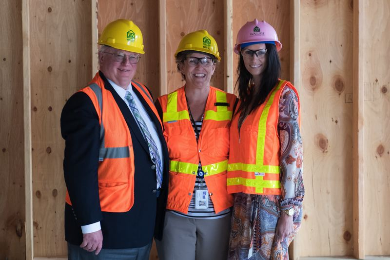STAFF PHOTO: CHRISTOPHER OERTELL - Cliff Walters (left) and daughter Jamie Ali (right) pose for a photo with Karen Hill, Cornelius' library director, during a tour of the Cornelius Place construction project on Monday, July 9.