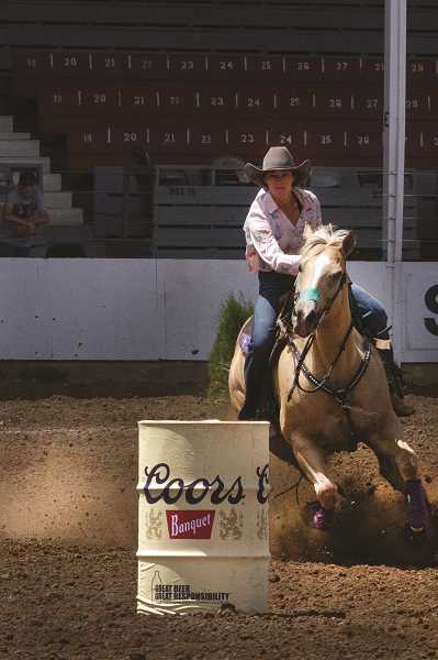 PATRICK EVANS - Cowgirl Darby Fox charges through the first turn in the Barrel Racing competition.