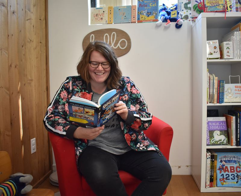 OUTLOOK PHOTO: TERESA CARSON - Sho Roberts owner of newly-opened Maggie Maes Kids Bookshop in downtown Gresham gets a laugh from one of the Dog Man books written by Dav Pilkey.