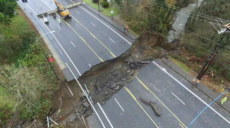 OUTLOOK FILE PHOTO - Heavy rain and a large flow of runoff in Kelly Creek in 2015 undermined a culvert, leading to a collapse of a 140-foot section of Kane Drive near Mt. Hood Community College. Though a temporary repair has been in place, workers are about to begin work on a permanent fix.