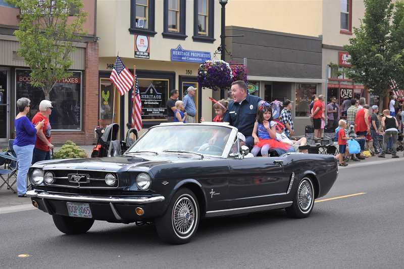 ESTACADA NEWS PHOTO: EMILY LINDSTRAND - Damon Faust, grand marshal of the 2018 Estacada Fourth of July Parade and the American Legions National Firefighter of the Year, and his daughters Henrietta and Faye cheerfully greet attendees of the event.