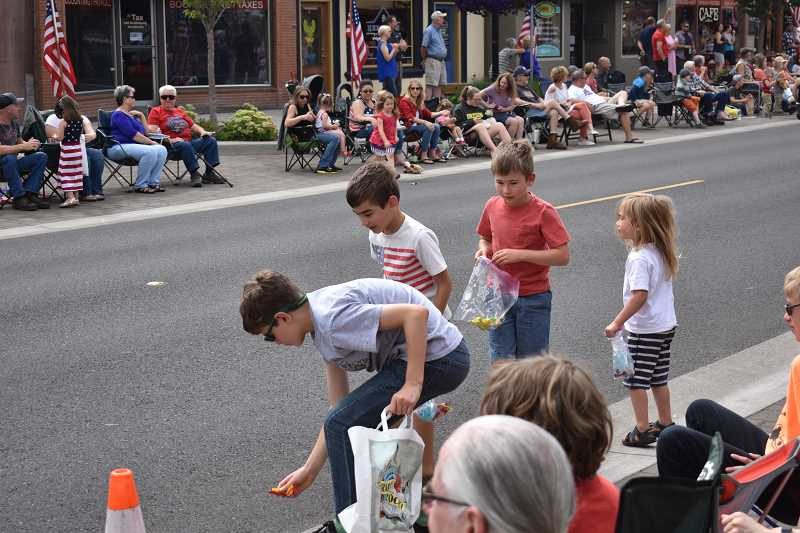 ESTACADA NEWS PHOTO: EMILY LINDSTRAND -  Young parade attendees search for candy on Wednesday, July 4.