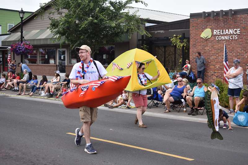 ESTACADA NEWS PHOTO: EMILY LINDSTRAND - Representatives from Portland General Electric Parks wear a boat and a camping tent during the parade through downtown Estacada on Wednesday, July 4.