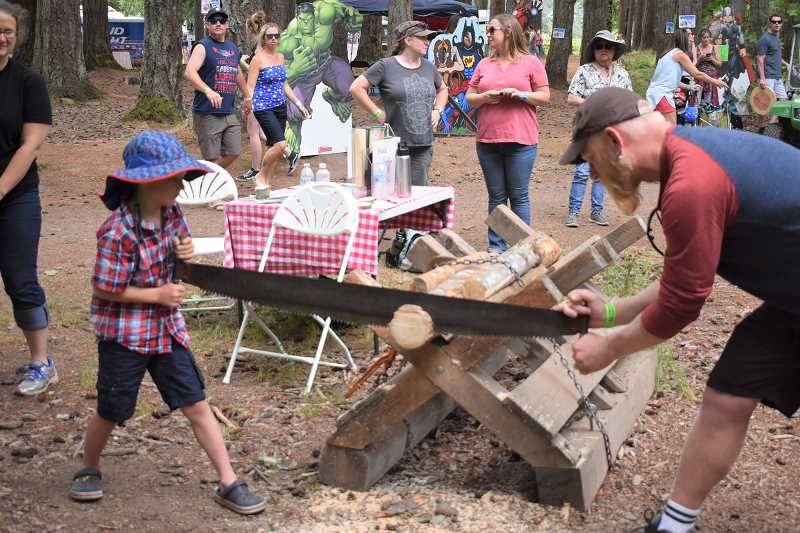 ESTACADA NEWS PHOTO: EMILY LINDSTRAND - Sawing was one of several activities children could participate in during the 2018 Estacada Timber Festival.